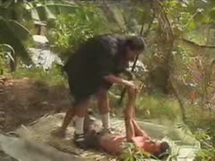 Two female dommes tormenting a slave in the forest