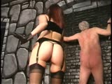Rope tied old man receives harsh whipping from a redhead domina