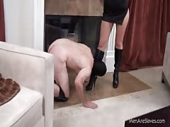 Ruthless blonde guiding slave with her whip while licking her boots