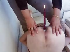 Mistress inserts candle on slave's asshole